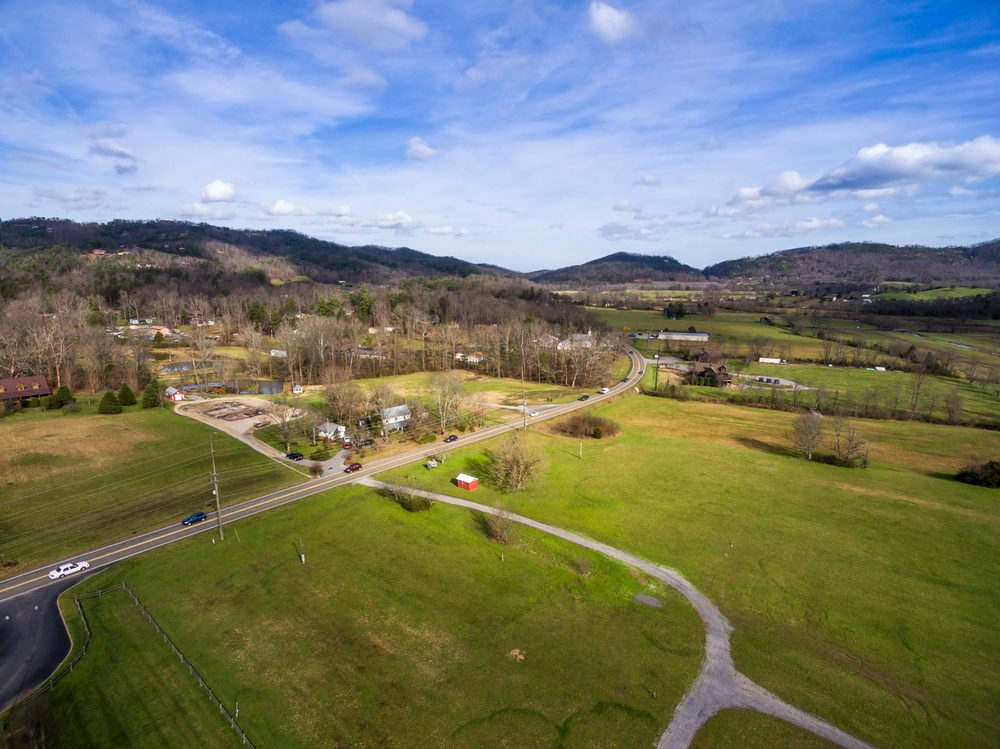 An aerial view of the small town of Townsend, one of the cutest small towns in Tennessee. It has a lot of green fields, smaller buildings, and you can see cars on the road. The trees don't have any leaves and you can see mountains in the distance.