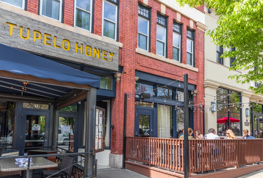 """The exterior of a brick building in a row of buildings. Above it is a sign that says """"Tupelo Honey' in yellow writing on a wooden background. There is a black tent with seating under it. There is also a patio with string lights over it where you can see people sitting and eating."""