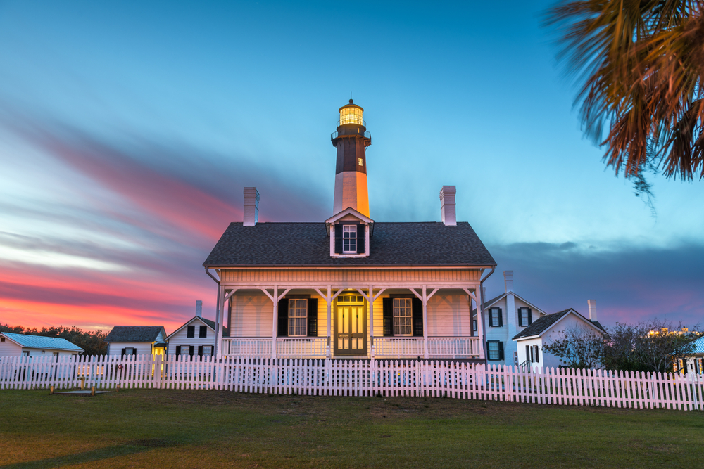 The lighthouse on Tybee Island. It is a small white house with black shutters and a front porch. Behind it is the striped black and white light tower. It is sunset and the sky is pink, blue, purple, and orange.