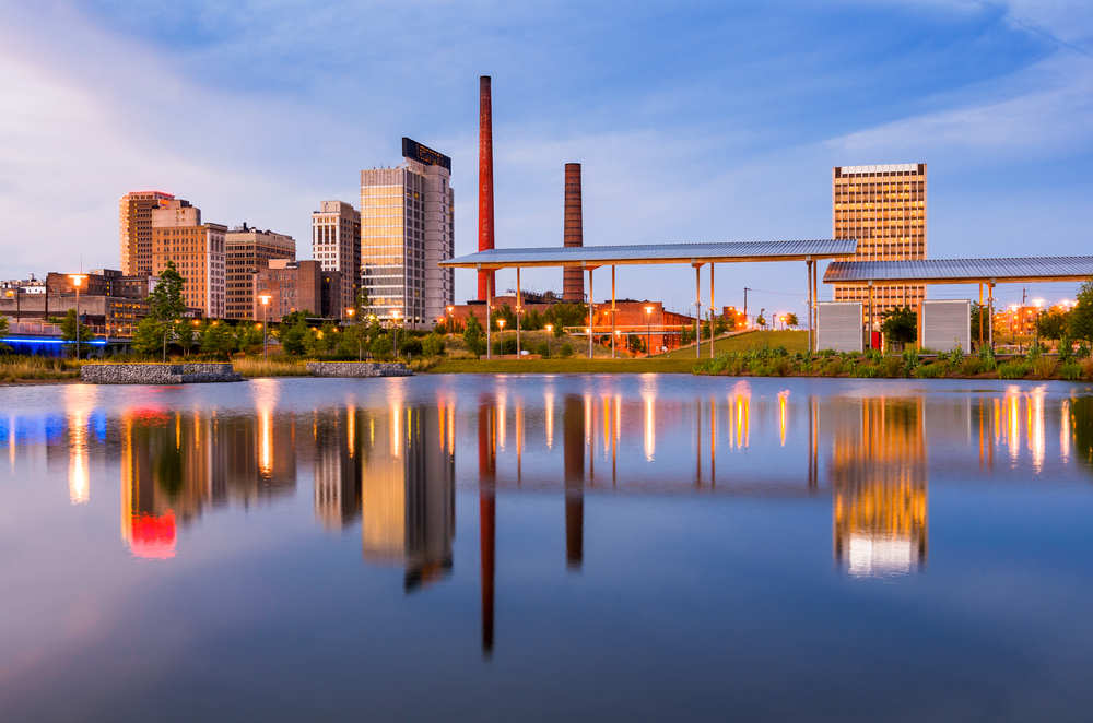 water in front of buildings and smoke stacks in Birmingham, Alabama
