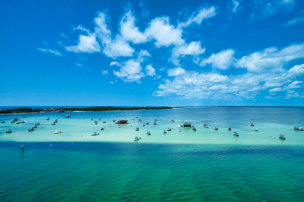 sand bar island with boats on top, different shades of blue water and bright blue sky