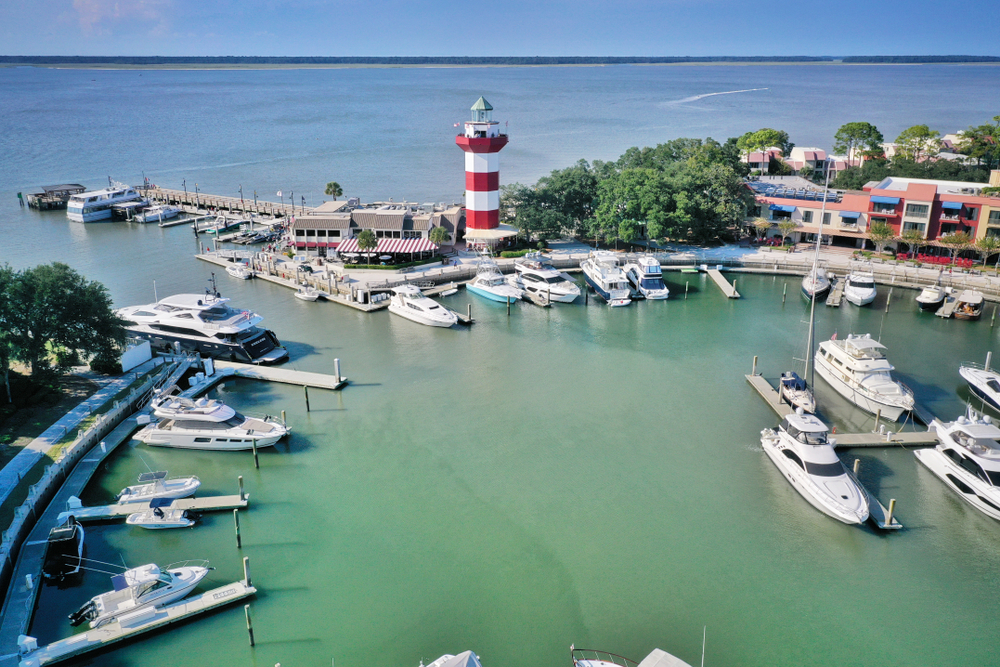 circular marina with boats parked inside, a red and white striped lighthouse by the water