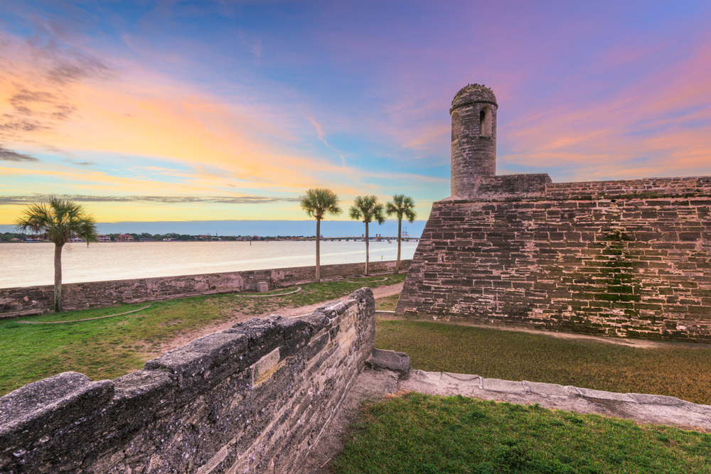 castle fort on waters edge, palm trees lining the water at sunset