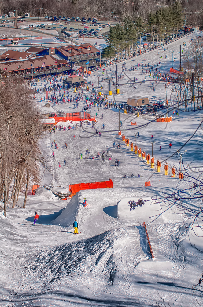A picture of crowds of people skiing and snowboarding in various snowy sections of the Appalachian Mountain Ski Resort on a sunny day.