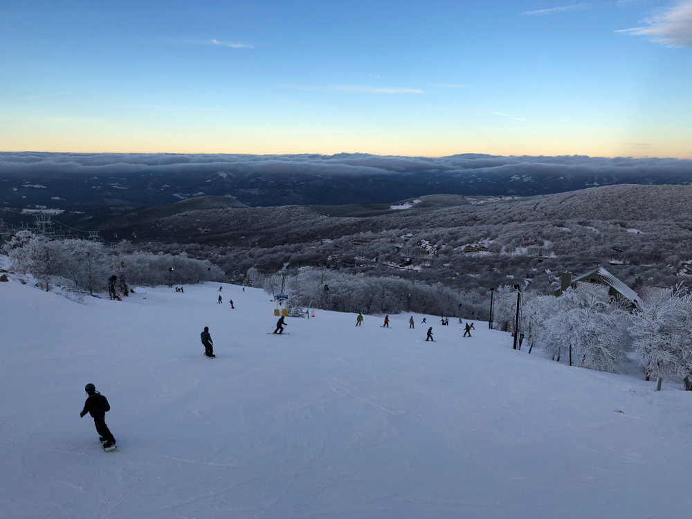 A picture snowboarders going down the side of a snowy bank at Beech Mountain Ski Resort with rolling hills and mountains in the distance.