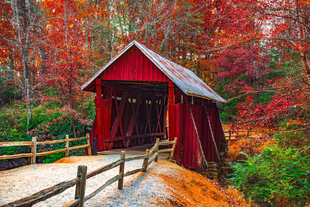 Photo of a red covered bridge with tin roof with a gravel going through it surrounded by fall foliage colored trees.