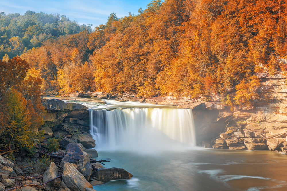 Photo of Cumberland Falls cascading downs the rocks into the Cumberland river with orange and gold trees along the sides during fall in the south