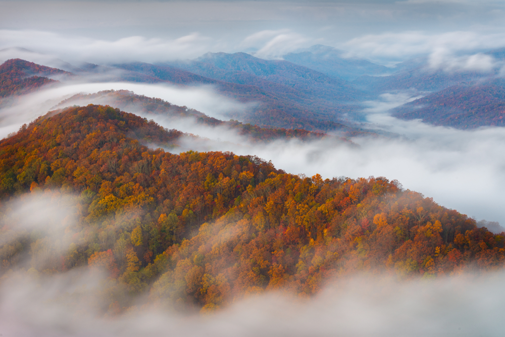 Aerial photo of fog moving over the fall foliage-covered mountains at Cumberland Gap State Historic Site during fall in the south