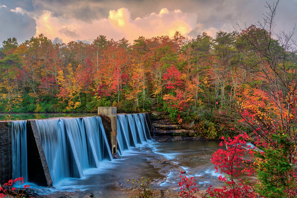 Photo of water cascading down the A. A. Miller Dam into a river below, surrounded by red, gold, and green trees