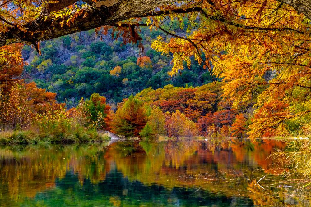 Photo of a hill covered in fall foliage and vibrant colored trees along the shore reflecting into a river at Garner State Park in Texas.