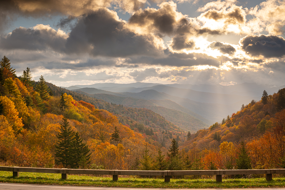Photo of a view from a pullout along Cumberland Gap Road in the Great Smoky Mountains with red and gold trees covering the mountains