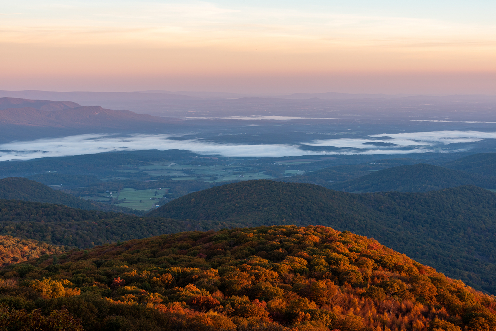 A picture of the view of the foggy valleys at sunrise from an overlook on Hogback Mountain.
