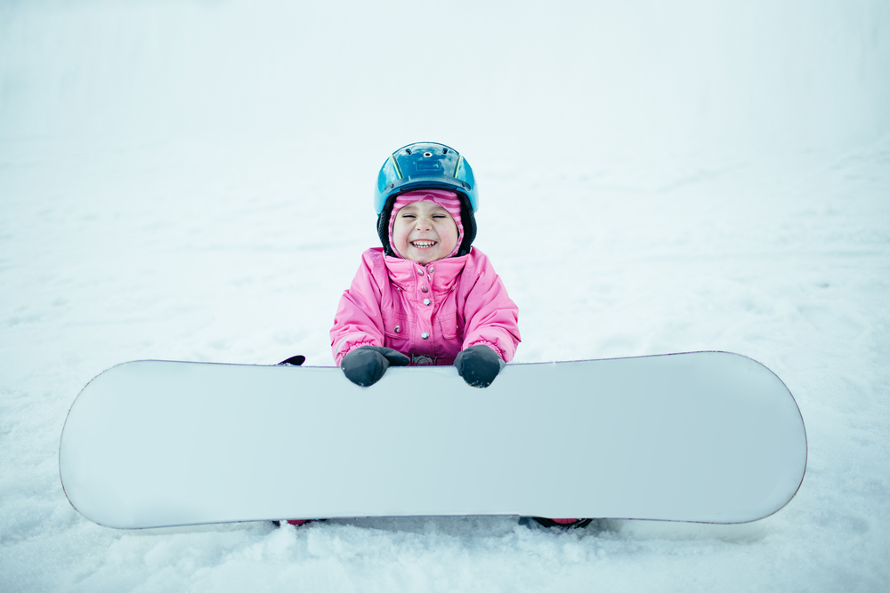 A photo of a child smiling who is wearing a blue helmet, sitting on snow, and holding a white snowboard.