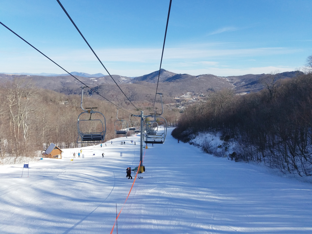 A picture of a ski lift above a snowy slope at Sugar Mountain Ski Resort.