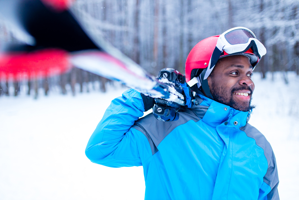A photo of a man smiling in a blue coat holding a pair of skis on a snowy day.