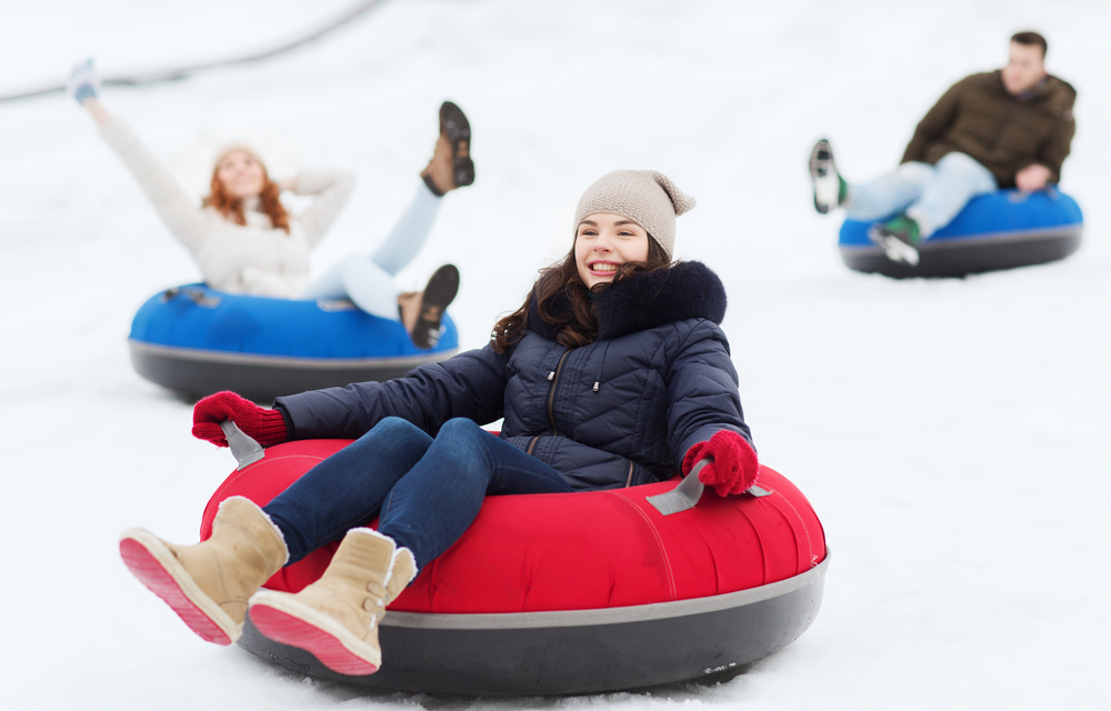A photo of a girl smiling in a black coat and brown shoes that is snow tubing down a hill on a red snow tube with two friends behind her in blue snow tubes.