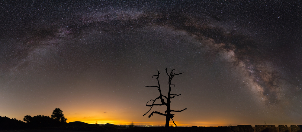 A panorama photo of the night sky capturing the milky way in Shenandoah National Park.
