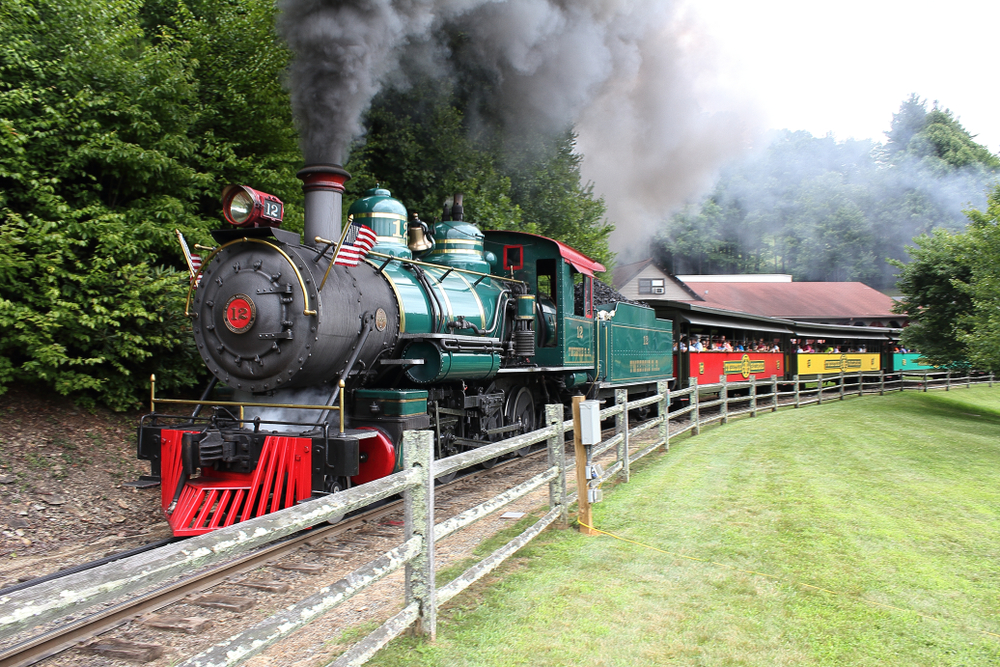 A picture of Tweetsie Railroad's steam train and the smoke bellowing from the front of it about to drive passengers away from the train station.