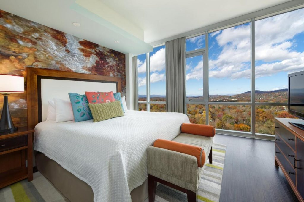 Photo of a room inside Hotel Indigo, with a colorful mural behind the bed and mountain views outside the floor to ceiling windows.