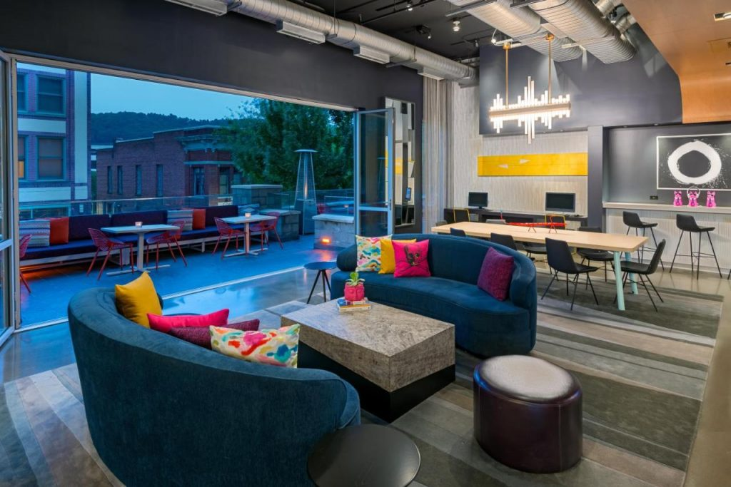 Photo of a common room inside Aloft Hotel with modern sofas, an outdoor patio area, and colorful decor.