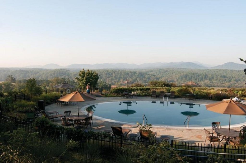 Photo of a swimming pool surrounded by patio tables with mountains in the background at The Inn on the Biltmore Estate.