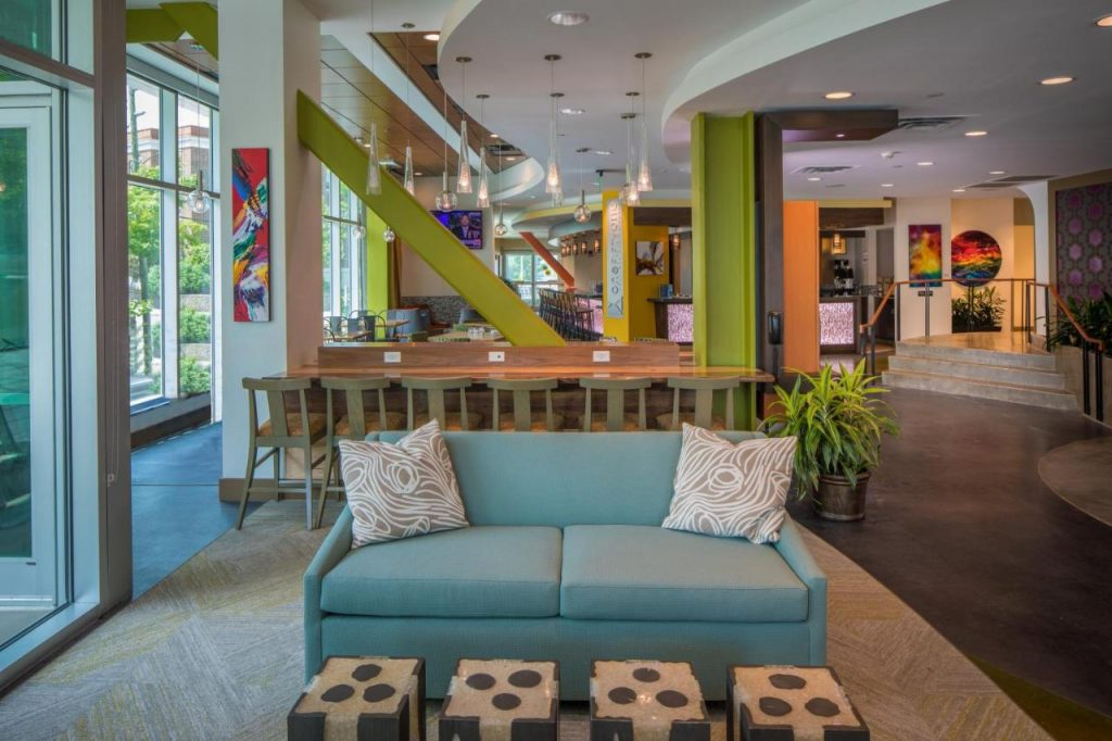 Photo of the lobby at Hyatt Place with colorful walls, modern blue sofa and bar area in the background.