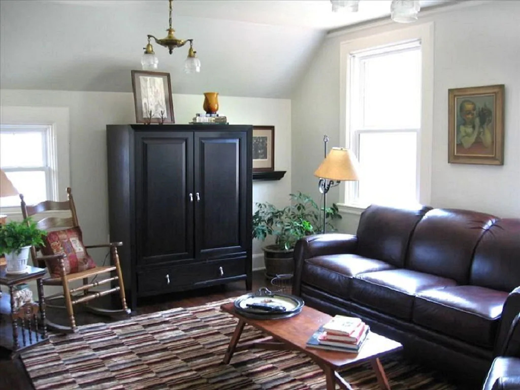 Photo of the living room in the Chapman House with a leather sofa, wooden cabinet, and antique decor.