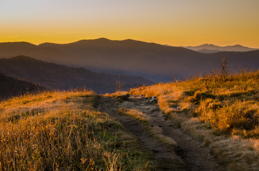 A well worn trail going over a mountain. The grass is dead around the trail and brown in color. In the distance you can see rolling mountains that are silhouetted against the sky. The sun is setting, so the sky is yellow and orange. It is one of the best Asheville hiking trails.