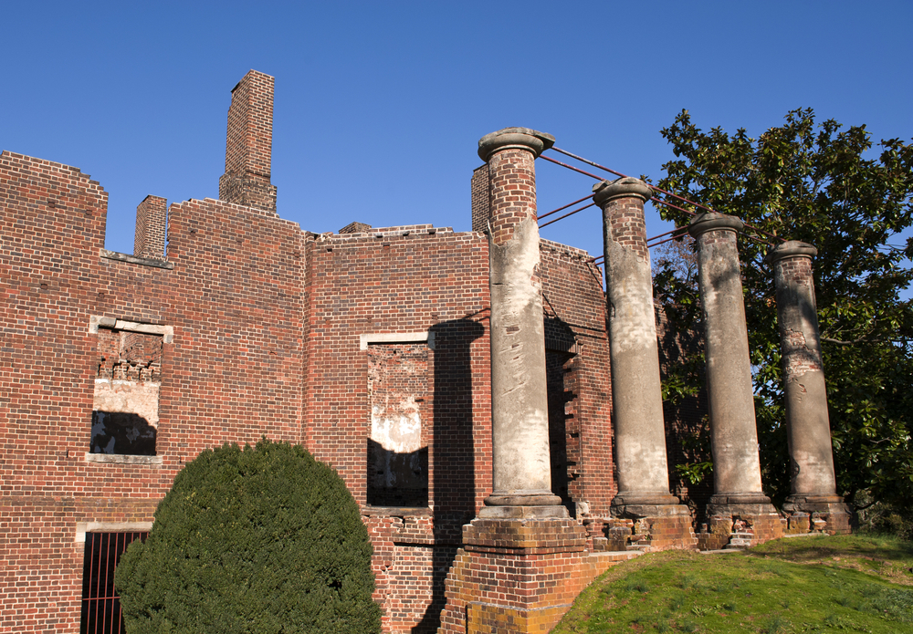 The ruins of a mansion that burnt down in 1884 in Virginia. The home was originally designed by Thomas Jefferson. You can see the brick exterior, four pillars made of brick and plaster, and trees and shrubs around it.