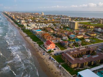 An aerial view of a beach town in Texas with houses a beach and the sea with small waves