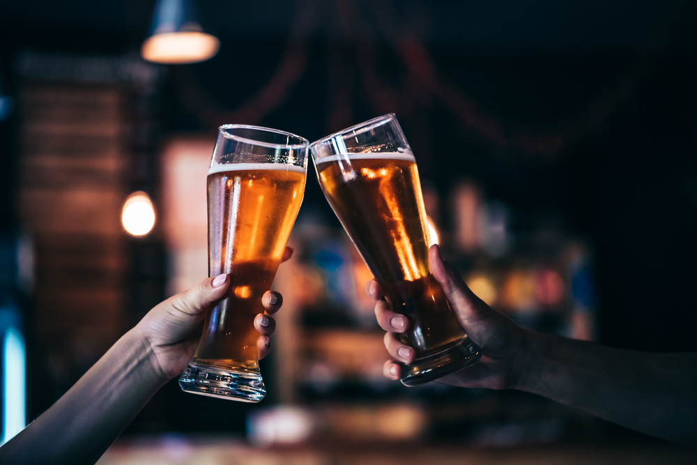 Two pint classes clinking together in an article about breweries in Asheville