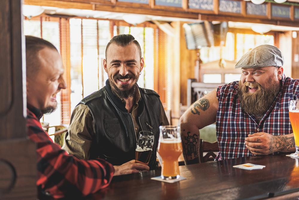 Three men drinking beer in a pub