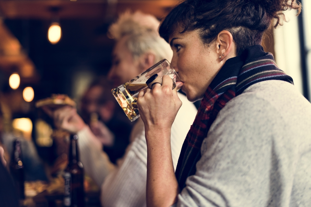 A women drinking a pink of beer in a pub