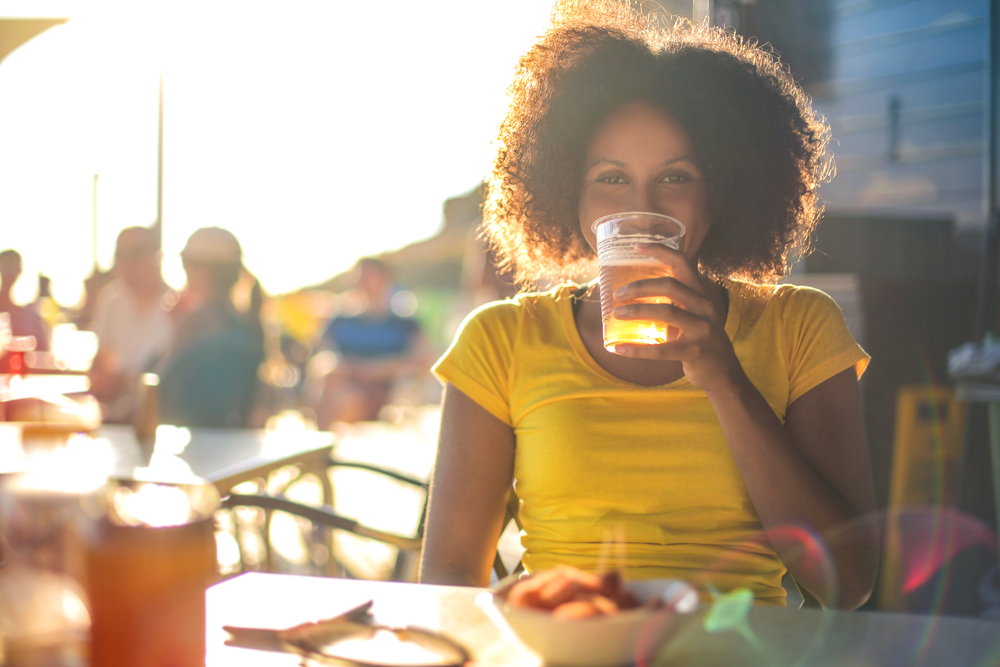 A women drinking a pint of beer on a patio