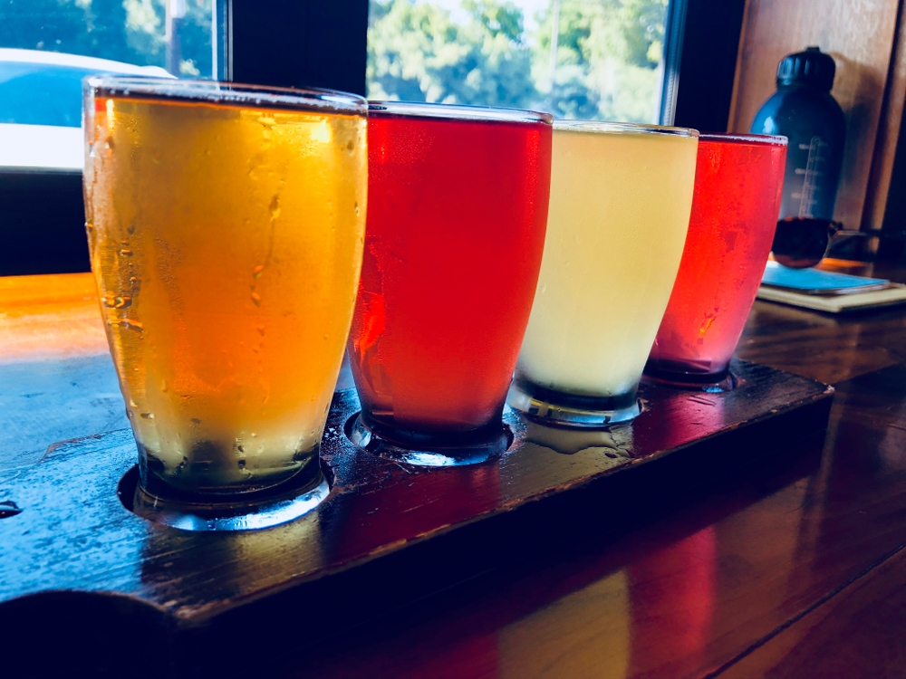 Four pints of beer on a bar in an article about breweries in Asheville