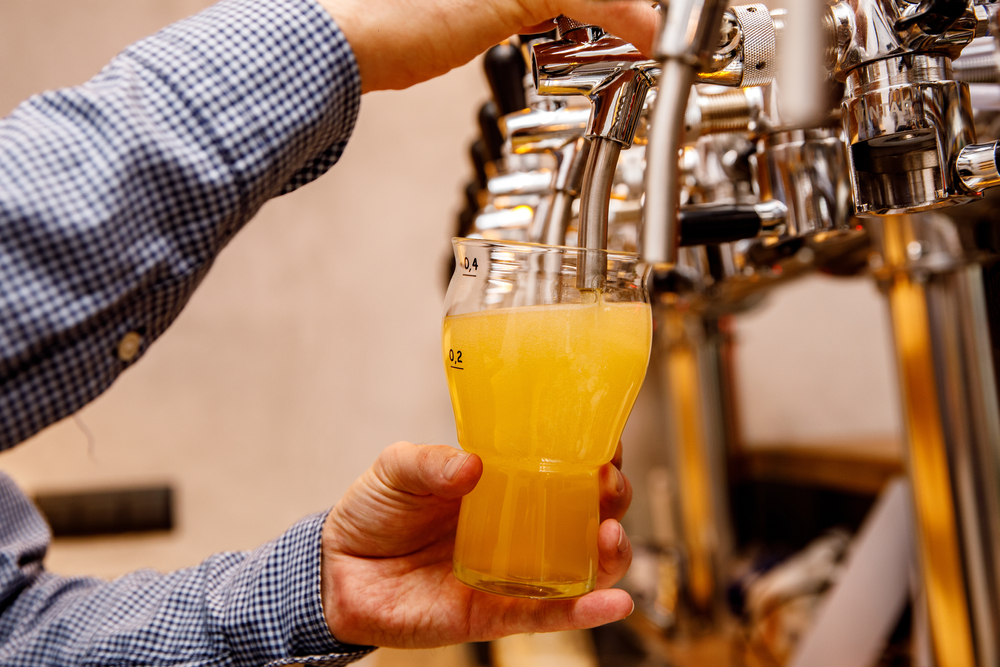 Bartender pouring a pink of beer in an article about breweries in Asheville