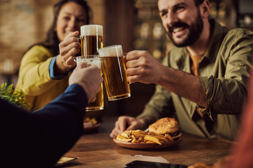 Three people drinking beer and eating in a pub