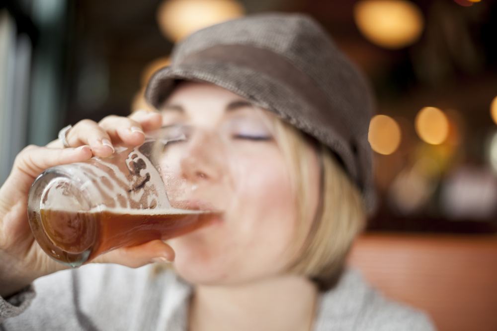 A woman in a hat drinking a pink of beer