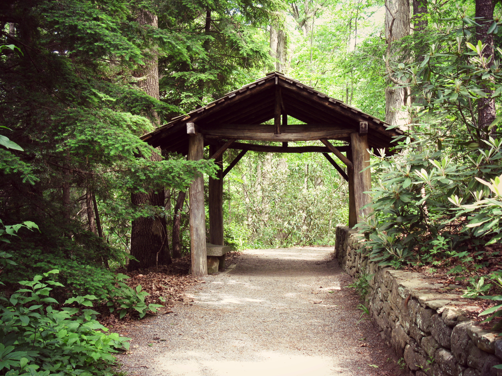 An old covered bridge on a dirt path. There is a stone wall and garden on one side of the path. On the other side of the path is a dense forest.