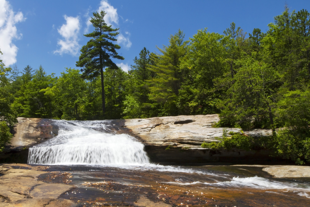 A waterfall flowing over a small rocky cliff into a thinner stream of water over a cliff slide. All around the waterfall there is a dense forest with green trees. The sky is bright blue with some clouds.