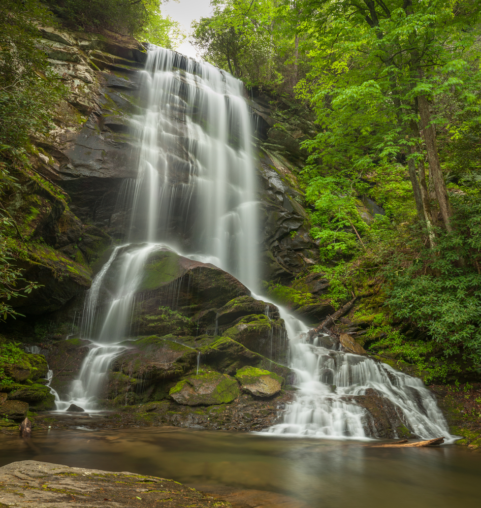 The large Catawba Falls. It is a large waterfall cascading down a rocky cliff side that falls almost straight down. It crashes on a few rocks that are sticking out. All around it is a dense forest with green trees. There is moss on the rocks.