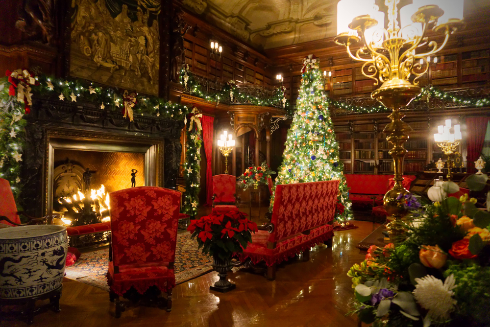 The inside of the library the Biltmore Estate. It is all decorated for Christmas with a Christmas tree, lit up boughs, and poinsettias.