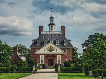 The exterior of the Governor's Palace in Colonial Williamsburg, one of the best Virginia day trips. It is a large brick building with a large ornate crest on a cream wall at the very front of it. There is a tower in the middle and several chimneys. It is surrounded by a green garden with shrubs.