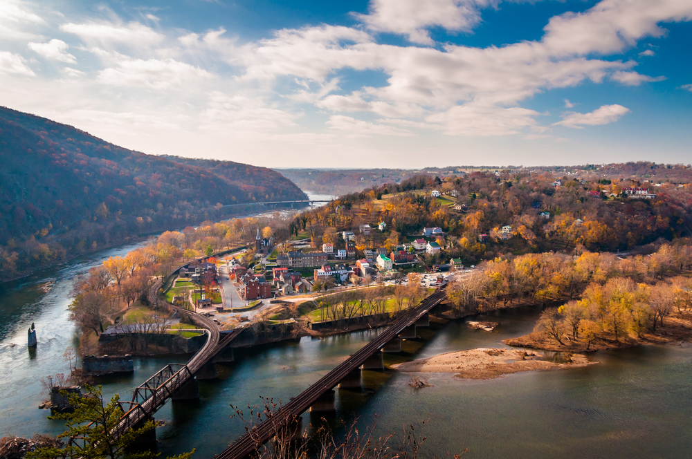 An aerial view of Harpers Ferry. You can see a bridge going across a river that leads to a small town on the side of a hill. The hillside is covered in trees with no leaves, or yellow and orange leaves. You can see the river in the distance running between the hills.