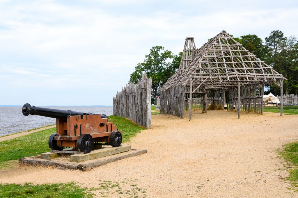 A structure made out of logs that looks like it's the frame of a building. It has sand underneath it and you can see a fence made of the same types of logs. You can also see an old canon that is next to a path on the beach.