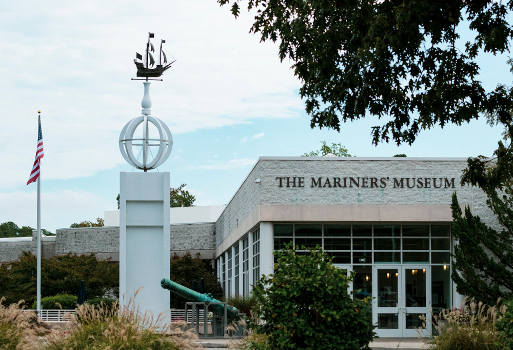 The exterior of the Mariners' Museum in Virginia. It is a white building with lots of windows, and there is a tall statue with a model ship on top of it. You can also see shrubs, tall grasses, and an antique canon.