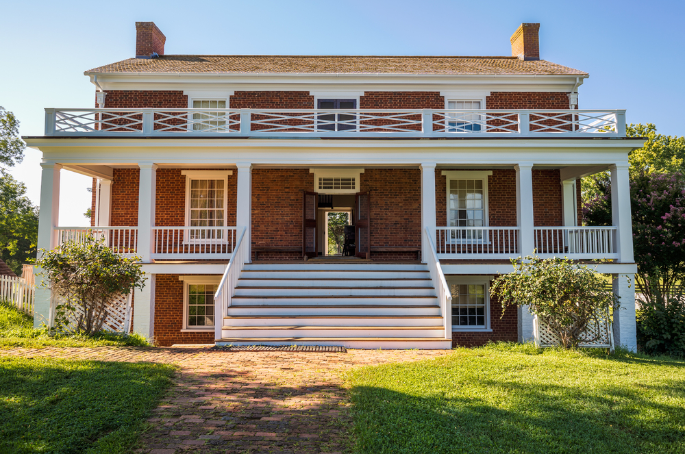 View of the front of Appomattox Courthouse with grassy lawn and open doors.