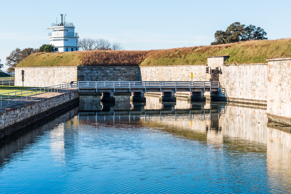 A glassy water filled moat with a bridge across it at Fort Monroe.