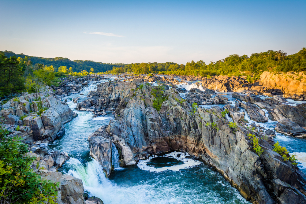 View of waterfalls and river at great falls park decided by large rock formations