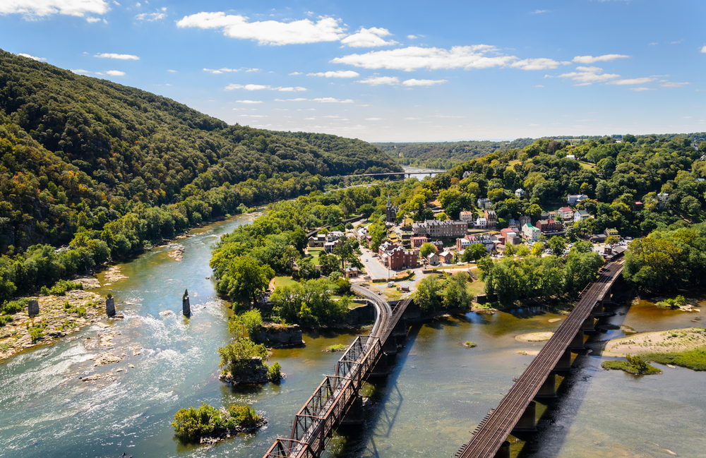 View overlooking the town and river and bridges at harpers ferry with a tree covered hill beside the river